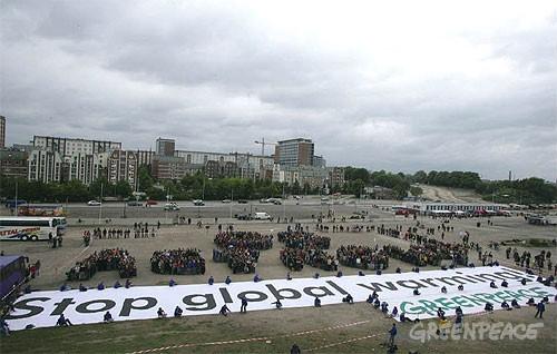 """mensaje """"G8, actúa ahora"""". Debajo del un pancarta que dice """"Parad el"""
